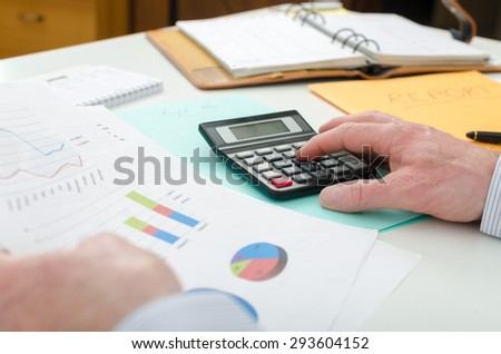 Businessman checking financial graphs, at the office - stock photo