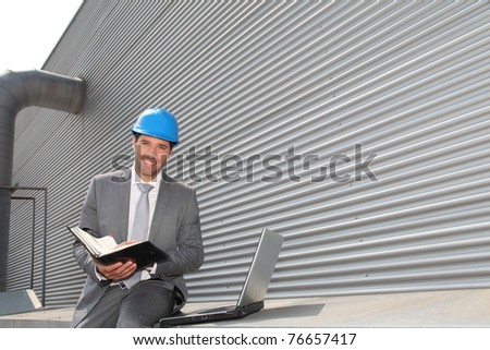 Businessman checking industrial installation - stock photo