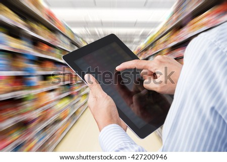 Businessman checking inventory in supermarket on touchscreen tablet. Motion blur Background