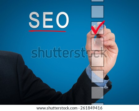 businessman checking mark on checklist marker. Checking SEO. Isolated on blue background, Stock Photo - stock photo