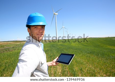 Businessman checking on wind turbine energy production - stock photo