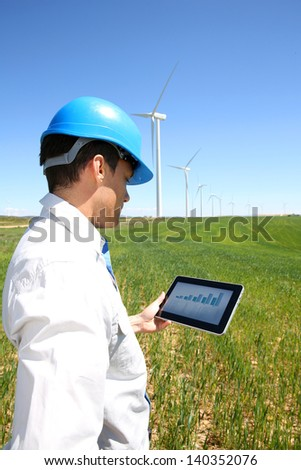 Businessman checking on wind turbine energy production