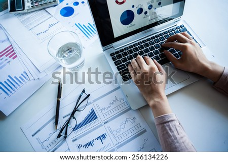 Businessman checking reported profits on the paper and laptop.