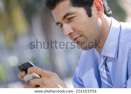 Businessman checking text messages on cell phone - stock photo