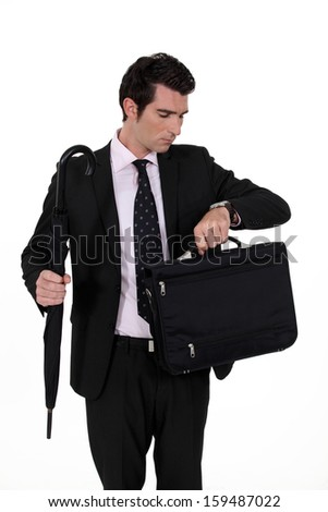 Businessman checking the time on wrist watch - stock photo
