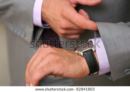 businessman checking time on his watch - stock photo