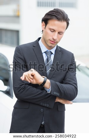 Businessman checking time outside his car - stock photo