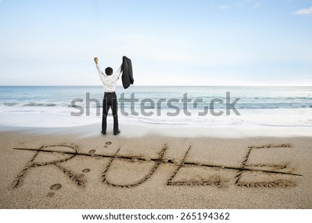 Businessman cheering with rule word deleted line written on sand beach background - stock photo