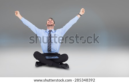 Businessman cheering with tablet sitting on floor against grey vignette - stock photo