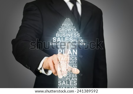 Businessman clicking on an upward arrow formed by business related words - stock photo