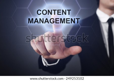 businessman clicks on virtual touchscreen display and select content management - stock photo