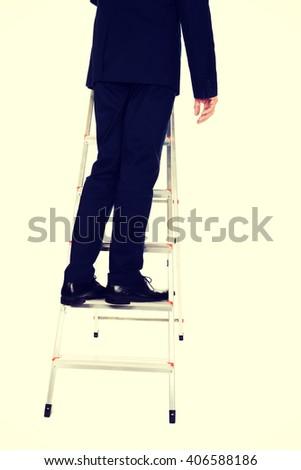 Businessman climbing ladder - stock photo