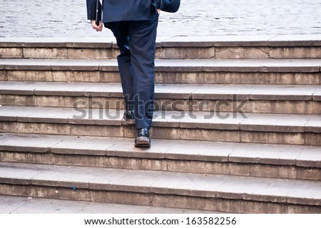 Businessman climbing stairs - stock photo