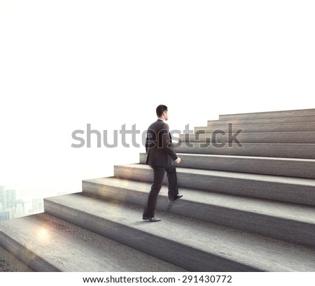businessman climbing to stairs on blue background - stock photo