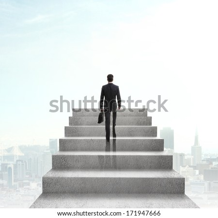 businessman climbing to stairs on city background - stock photo