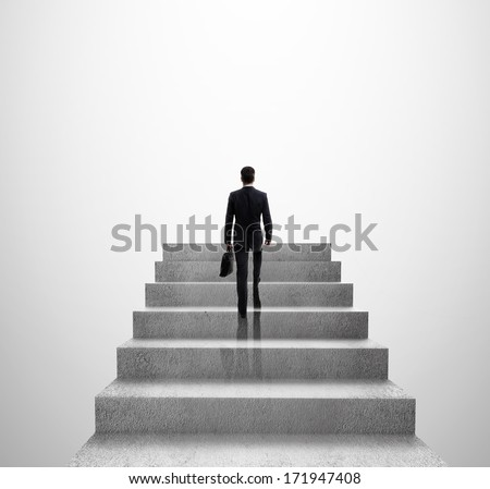 businessman climbing to stairs on gray background