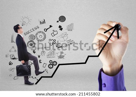 Businessman climbing upward chart to gain her business target by following businessman's hand - stock photo