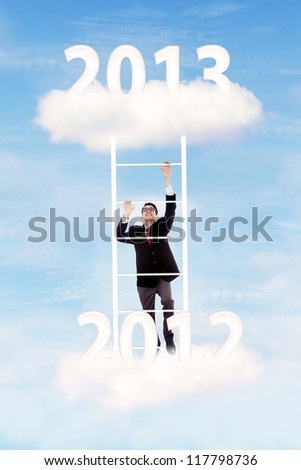 Businessman climbing upward on the stair of cloud from the year of 2012  to 2013 to gain his success