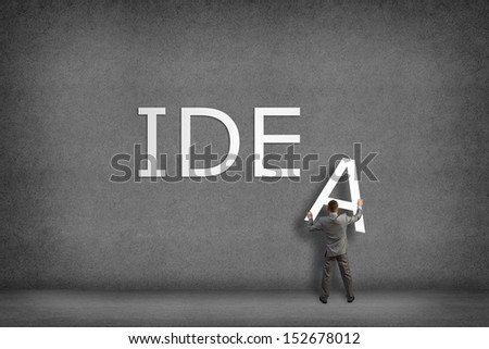 Businessman collects on the wall the word idea, places the letter on the wall - stock photo