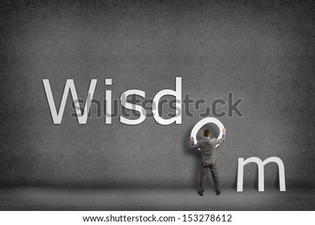 Businessman collects on the wall the word wisdom, places the letter on the wall - stock photo
