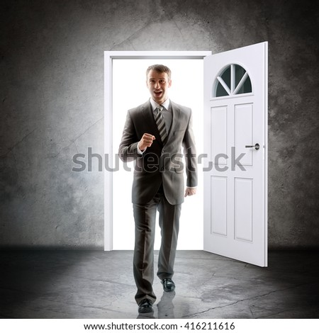 Businessman comes inside through door. Behind door bright light. Success concept