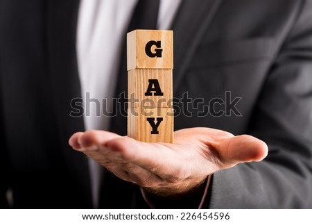 Businessman coming out of the closet and announcing that he is gay holding a stack of wooden alphabet cubes in his hand with the text - Gay, close up view. - stock photo