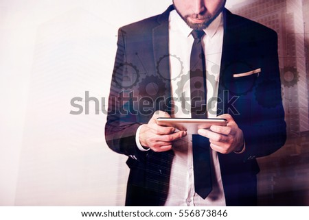 Businessman communicating on a tablet, human connection concept, modern building in the background.
