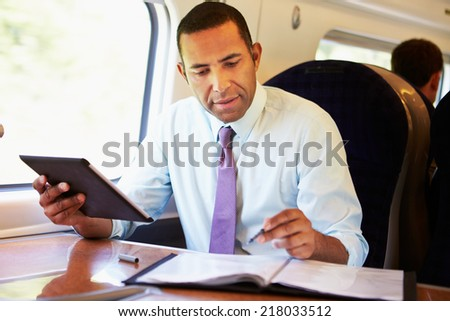 Businessman Commuting On Train Using Digital Tablet - stock photo