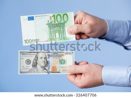 Businessman comparing hundred dollars and hundred euro, blue background - stock photo