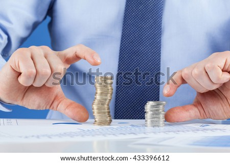 Businessman comparing stacks of coins, closeup shot - stock photo