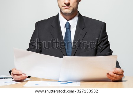 Businessman comparing two documents, neutral background - stock photo
