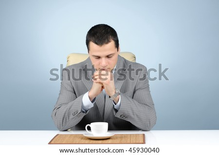 Businessman concentrating on successful business over a cup of coffee on gray background - stock photo