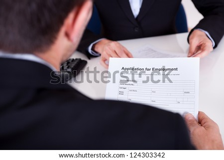 Businessman conducting an employment interview with an over the shoulder view of an application form - stock photo