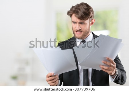 Businessman confused with a lot of paperwork