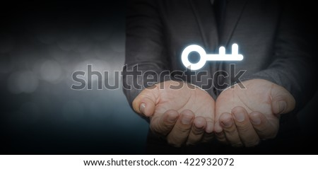 Businessman (consultant, coach, leader, CEO or another business person) offer key to success. Turnkey solution and services concept, bokeh in background. - stock photo