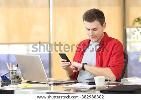 Businessman consulting a smart watch and mobile phone sitting in a desk at office