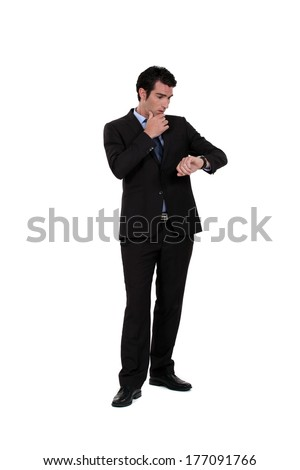 Businessman consulting his watch - stock photo