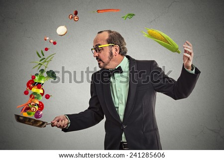 Businessman cooking vegetables with a pan isolated on grey wall background. Positive face expression emotion. - stock photo