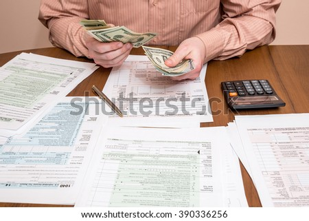 businessman counting dollars on background of tax forms - stock photo