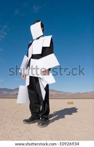 Businessman covered with white papers - stock photo