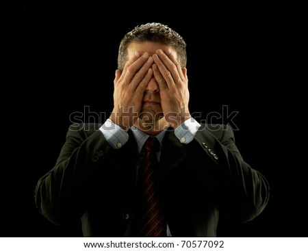 Businessman covering his eyes on black background. Businessman on black background. - stock photo