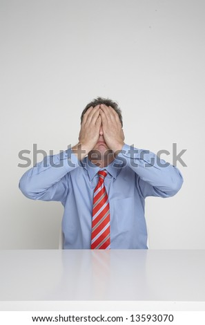 Businessman covers his face in desperation - stock photo