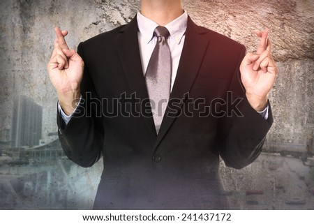 businessman crossing his fingers. - stock photo