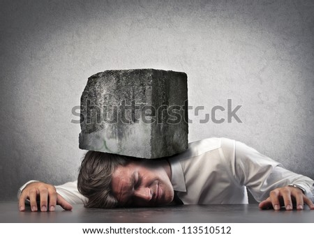 Businessman crushed by a boulder - stock photo