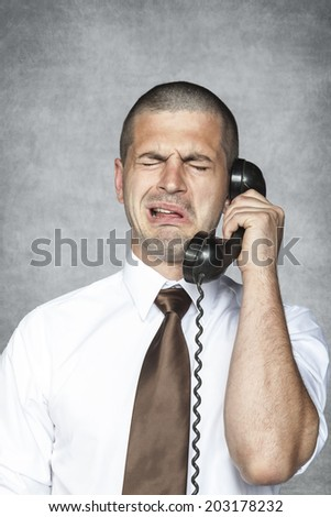 businessman crying while talking on the phone - stock photo