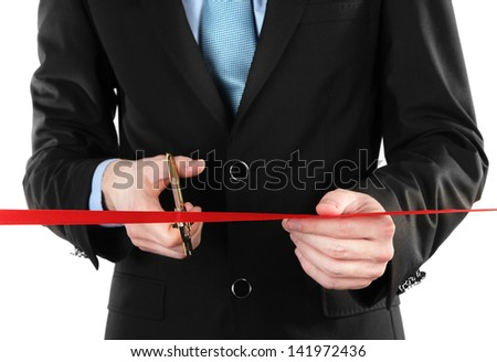 Businessman cutting red ribbon with pair of scissors close up - stock photo