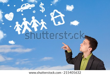 Businessman daydreaming with family and household clouds on blue sky - stock photo