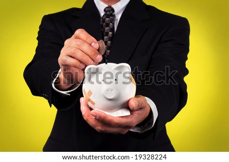 Businessman depositing coin in a piggy bank