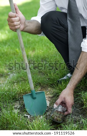 Businessman digging savings, unrecognizable person