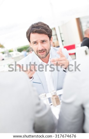Businessman discussing with colleagues at sidewalk cafe - stock photo